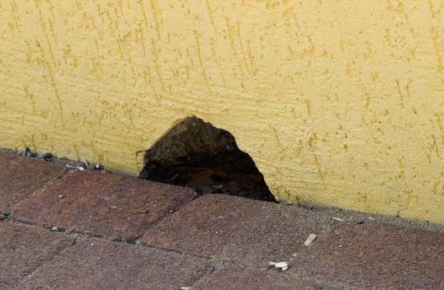 дыра в стене желтого фасада дома